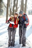 Hikers couple looking for path on map. In wood on winter Stock Images