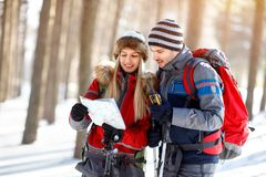 Hikers couple looking for path on map. In wood on winter Royalty Free Stock Photo