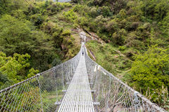 Hikers crossing a long metal suspension bridge Stock Photography