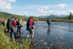 Hikers crossing mountain river Stock Photos