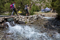Hikers crossing river Royalty Free Stock Images