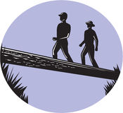Hikers Crossing Single Log Bridge Oval Woodcut Stock Image