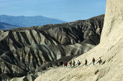 Hikers At Death Valley. A view of several hiker through rugged countryside along a trail passing through Golden Canyon in Death Valley National Park, California Stock Photo