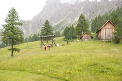 Hikers descend to the valley from the mountains of the Dolomites. Alps, through green fields Royalty Free Stock Images