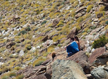 Hikers in desert look at distant object stock images