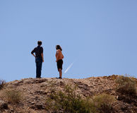 Hikers in desert point to aircraft trail royalty free stock image