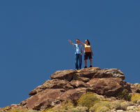 Hikers in desert point to distant object royalty free stock images