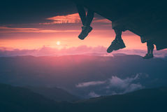 Hikers enjoy sunset. Instagram stylisation. Hikers sit on a wooden flooring above the mountain valley and enjoy sunset. Instagram stylisation Royalty Free Stock Images