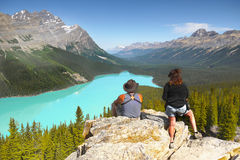 Hikers Enjoying Mountains View. Unknown hikers enjoying the view of the mountains and turquoise lake. Banff NP, Alberta, Canada. Taken in June 2015 stock photos
