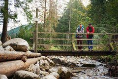 Hikers enjoying the view from a bridge in the forest Royalty Free Stock Images