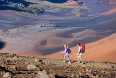 Hikers enjoying walk on amazing mountain trail. Backpacking in Haleakala volcano, incredible view. Couple trekking Stock Photography