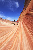 Hikers Entering The Wave — portrait. Two hikers enter the petrified sandstone formations at The Wave in the Coyote Buttes section of the Paria Canyon Stock Photography