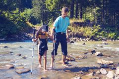 Hikers - father and small son walk across mountain river. Holding hands on a sunny day. Awesome travel in wilderness with family Stock Photography