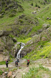 Hikers in front of waterfall Stock Images