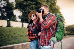 Hikers go sightseeing and makes photo for memory. Hikers with backpacks go sightseeing in tourist town and makes photo for memory. Summer hiking. Hike adventure royalty free stock image