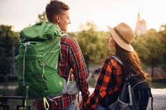 Hikers go sightseeing in tourist town on vacation. Hikers with backpacks go sightseeing in tourist town on vacation. Summer hiking. Hike adventure of young men royalty free stock image