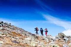Hikers go up high in the mountain Royalty Free Stock Image