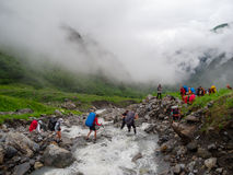 Hikers group cross the mountain river. Ford Royalty Free Stock Photos