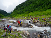 Hikers group cross the mountain river. Ford Royalty Free Stock Photo