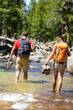 Hikers group walking barefoot crossing river. In forest. Adventure people on hike hiking in nature holding shoes and boots to cross with wet feet Royalty Free Stock Image