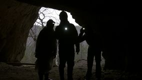 Hikers in helmets silhouettes enters to explore the dark cave with flashlights. Telephoto shot stock video