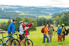 Hikers helping cyclists following track nature landscape Royalty Free Stock Photography