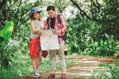 hikers hiking смотрящ карту Пары или друзья проводя совместно усмехаться счастливый во время располагаясь лагерем похода перемеще Стоковые Изображения