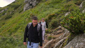 Hikers hiking in beautiful landscape. Man and women trekking walking with backpacks in mountains.  stock footage
