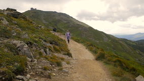 Hikers hiking in beautiful landscape. Man and women trekking walking with backpacks in mountains.  stock video