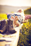 Hikers hiking boots Bank meadow. Hiker lying with walking boots on bench and meadow Royalty Free Stock Image