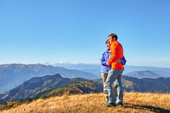 Hikers hiking enjoying view looking at mountain landscape Stock Photo