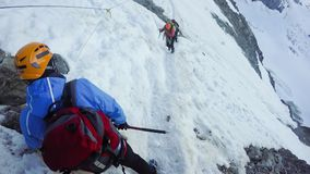 Hikers at hiking expedition toward Mont Blanc on Alps mountains in France. Passing the dangerous couloir. Many people lost theris lives at this point royalty free stock image