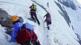 Hikers at hiking expedition toward Mont Blanc. N Alps mountains in France. Passing the dangerous couloir. Many people lost theris lives at this point stock photos