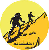 Hikers Hiking Up Steep Trail Circle Woodcut. Illustration of hikers with hiking stick hiking up a steep trail set inside circle done in retro woodcut style Royalty Free Stock Photos