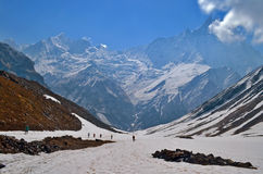 Hikers in Himalayan mountains. Nepal, Annapurna region, Annapurna Base Camp track. View of Machapuchare peak. Royalty Free Stock Photo