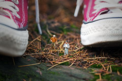 Hikers and huge sneakers. Miniature hikers and huge Sneakers Stock Images