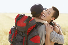 Hikers Hugging In Field Stock Images