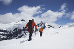 Hikers Joined By Safety Line In Snowy Mountains Stock Photos