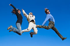 Hikers jumping cheerfully on mountain summit Royalty Free Stock Image