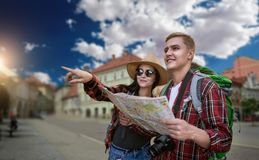 Hikers looking for city attractions on the map royalty free stock photography