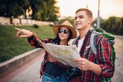 Hikers looking for city attractions on the map stock photography
