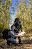 Hikers who study the way along a path nestled in the forest royalty free stock photo