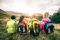 Hikers looking at sunset. Four backpackers looking at sunset over the mountains - Hikers talking and relaxing after an excursion in the nature - Friends enjoying Royalty Free Stock Images