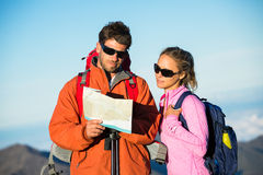 Hikers looking at trail map. Hiking in the mountains Stock Images