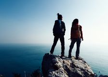 Hikers looking at the view on seaside mountain top rock edge. Two women hikers looking at the view on seaside mountain top rock edge Stock Photos