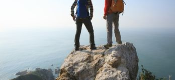 Hikers looking at the view on seaside mountain top rock edge royalty free stock images