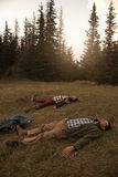 Hikers lying on the grass after a long wilderness trek Stock Images