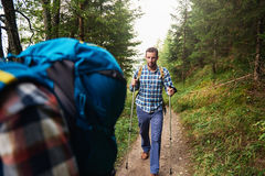 Hikers making their way along a forest trail Stock Photos