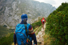 Hikers makng their way along a trail in the mountains Royalty Free Stock Images