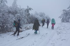 Hikers marching by a misty snowbound road Stock Photo